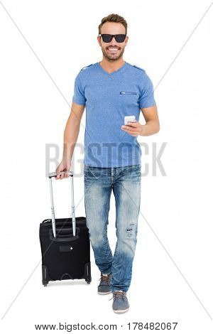 Young man with trolley bag and mobile phone on white background