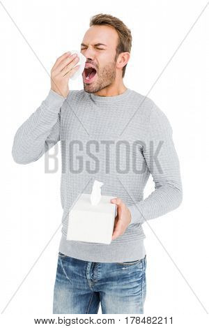 Young man holding a tissue and sneezing on white background