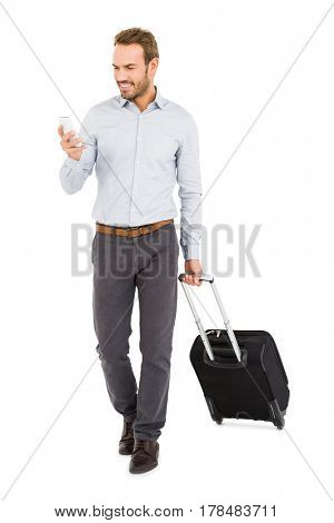 Happy young man holding trolley bag and using mobile phone on white background