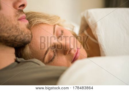 Cute couple sleeping on their bed in the bedroom