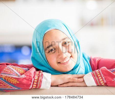 Muslim girl smiling at home indoors