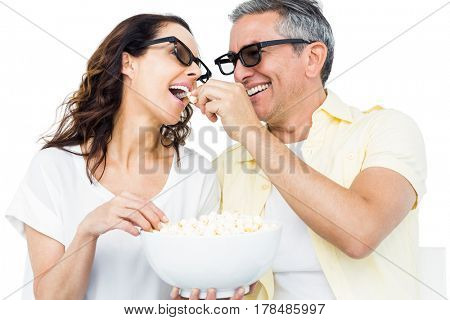 Smiling couple with 3D glasses eating popcorn over white background