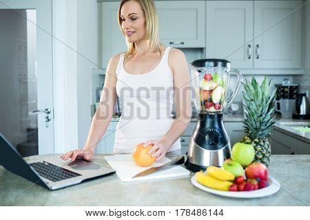 Pretty blonde woman preparing a smoothie with recipe on laptop in the kitchen