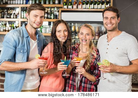 Friends toasting with cocktails while standing up at bar