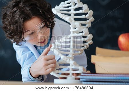 Exploring world of microbiology . Smart enthusiastic little researcher standing in the laboratory and looking at genetic code model while studying bioengineering and working on the project
