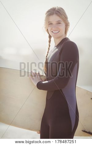 Happy woman in wetsuit holding a surfboard on the beach on sunny day