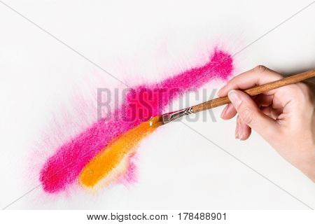 hand with a brush draws paints with watercolors red and yellow line