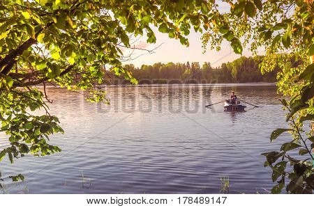 A young guy rides a boat on a lake during sunset. Man rowing in golden hour