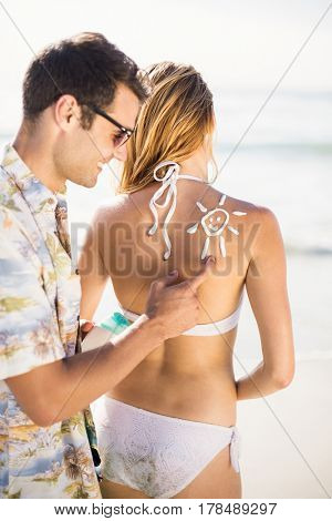 Man making a sun symbol on womans back while applying a sunscreen lotion at the beach