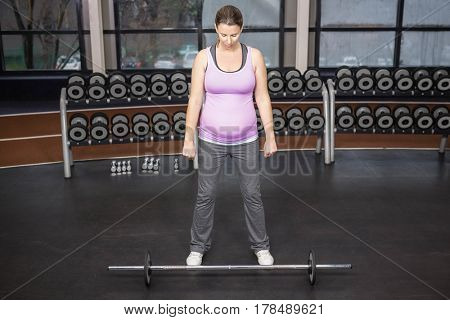 Determined woman looking at barbell at the gym