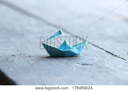 paper boat on old wooden table, travel idea