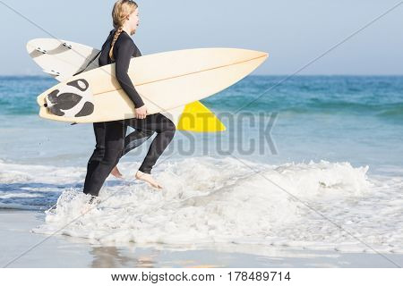 Woman in wetsuit carrying a surfboard and running towards sea