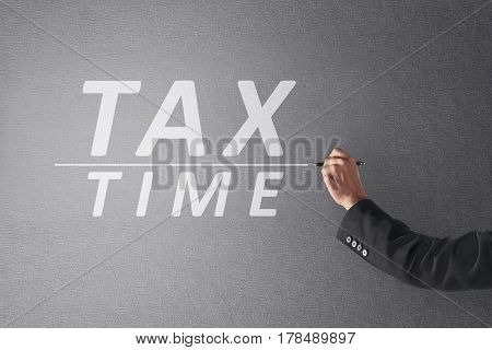 Business Person Hand Writing Tax Time With Pen