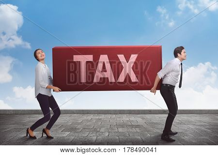 Business teamwork carrying heavy tax burden with sky background
