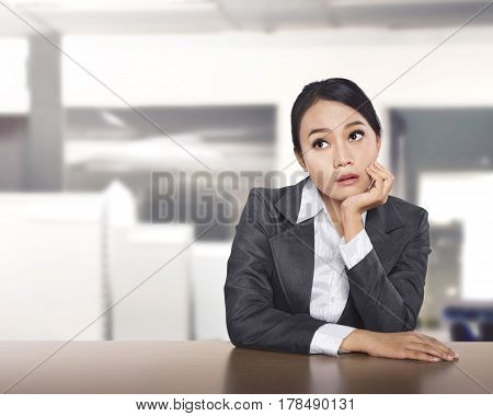 Young Asian Business Woman Working At Office Desk And Thinking Something