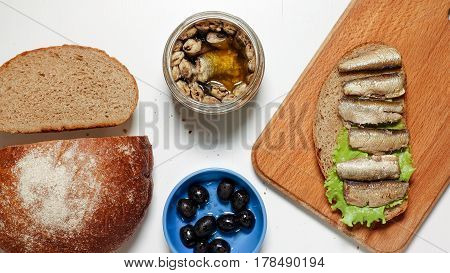 Sardines, sprats on a piece of black bread with a leaf of lettuce on a board, near black bread, olives and a jar with fish