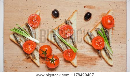 Triangular sandwiches with sardines, sprats, cherry tomatoes and green onions, olives