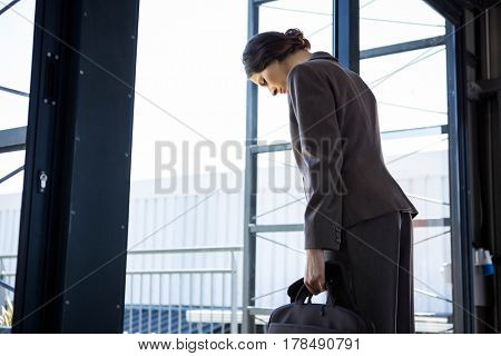 Tired businesswoman leaving office with laptop bag in her hand