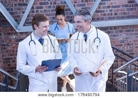 Doctors discussing medical report on staircase in hospital