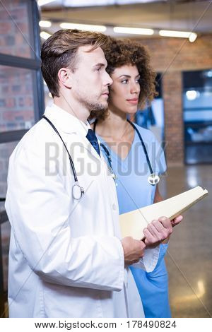 Doctor and nurse standing in hospital with medical report