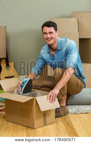 Young man unpacking carton boxes in his new house