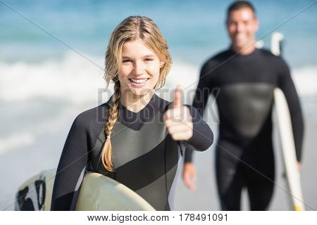 Happy woman with surfboard showing her thumb up on the beach