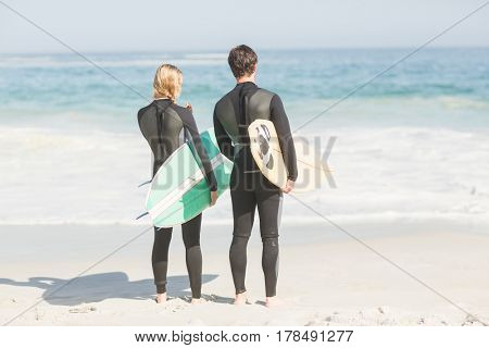 Rear view of couple in wetsuit with surfboard standing on the beach on a sunny day