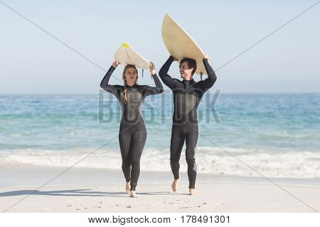 Happy couple in wetsuit carrying surfboard over the head on the beach