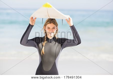 Portrait of woman in wetsuit carrying surfboard over head on the beach