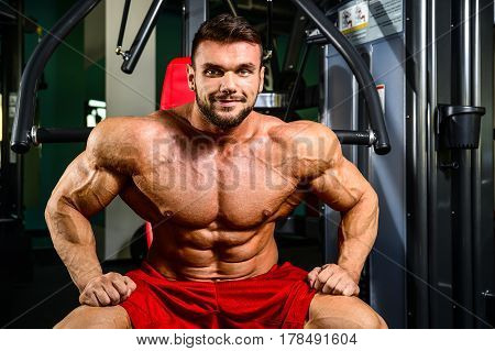 Handsome fit caucasian muscular man flexing his muscles in gym on diet. Brutal bodybuilder powerful training and execute exercise