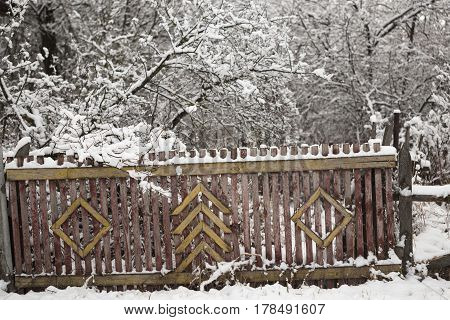 Wooden House In A Village With A Fence Under The Snow