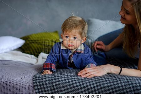 Amusing little boy lies on a big bed. Near him his young mother. She tenderly and carefully concerns the kid. Boy has a cute serious face beautiful big eyes.