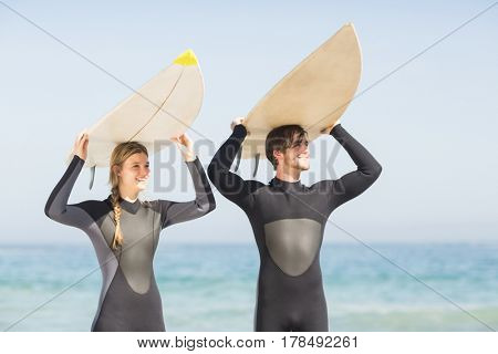 Happy couple in wetsuit carrying surfboard over head on the beach