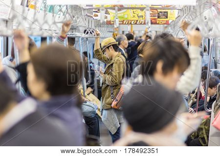 Tokyo, Japan - November 6, 2015: Crowds of daily commuters taking metro ride from work, standing and waiting inside public transport on November 6th in Tokyo, Japan, 2015.