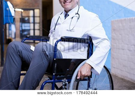 Male doctor sitting on wheel chair in hospital