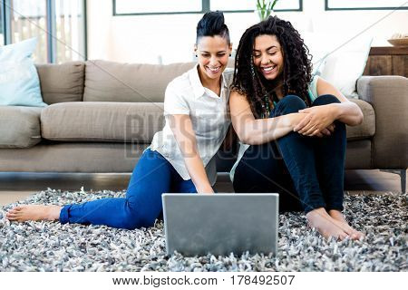 Smiling lesbian couple sitting on rug and using laptop in living room