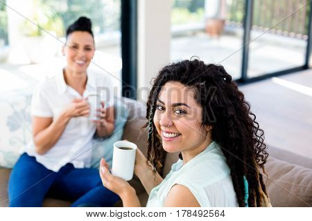 Lesbian couple smiling while having a cup of coffee
