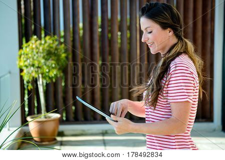 smiling Woman standing outside on her tablet