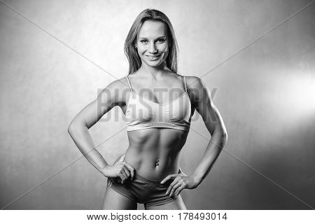 Portrait Of Beautiful Young Fit Woman Studio On Gray Background