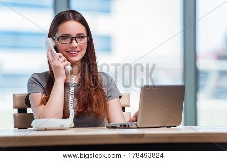 Young woman talking on phone in office