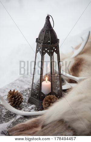 Black lantern with white candle burning