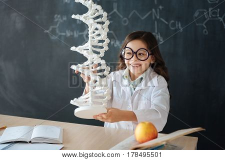 Exploring genetic code modifications. Gifted smiling little girl sitting in the lab and enjoying microbiology class while studying and holding the genetic code model poster