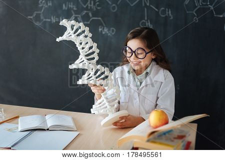 Exploring genetic code mutation. Skilled happy little pupil sitting in the lab and enjoying microbiology class while studying and exploring chromosome model