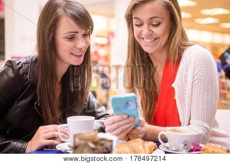 Two women looking at mobile phone while having snacks and coffee in coffee shop