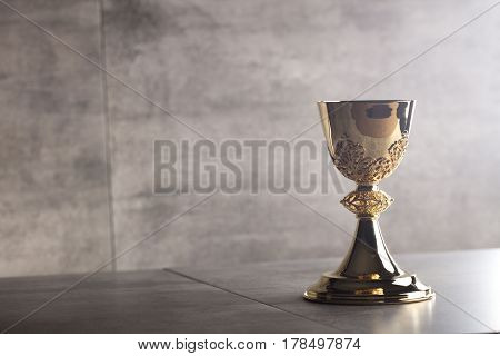 Catholic religion theme.  Gold chalice on stone table and stone background.