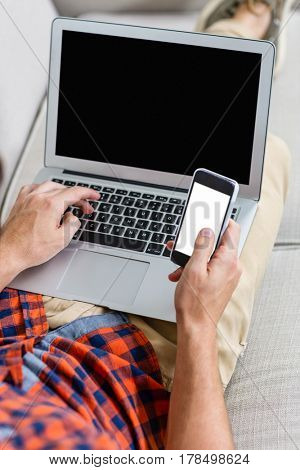 Handsome man using laptop and smartphone on couch in living room