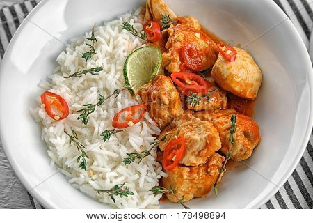 Plate with chicken tikka masala and rice in white bowl