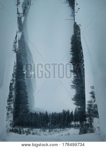 Surreal view over the Carpathian mountains. Windy winter day and snow covered fir trees. Symmetry three dimensional landscape holiday journey travel concept.