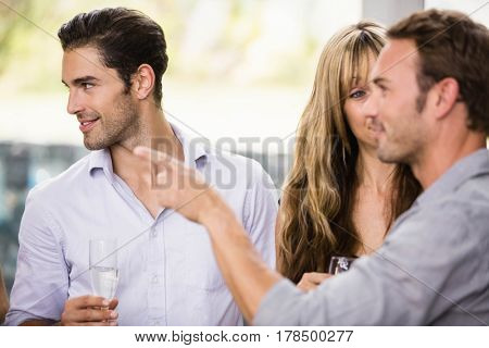 Friends having champagne and talking to each other at a party