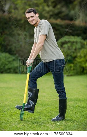 Portrait of young man standing with a gardening rake in garden